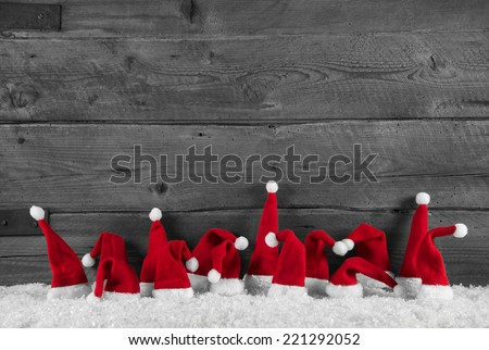 Humorously red, grey and white wooden christmas background with santa hats. - stock photo