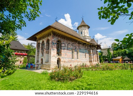 HUMORULUI, ROMANIA - 8 AUGUST 2014: Old traditional Orthodox Humorului Monastery Church in Moldavia Region of Romania with painted walls with religious scenes unique in the world for being so beautiful. - stock photo