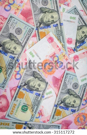 Hundred banknote of Chinese currency yuan and American dollars