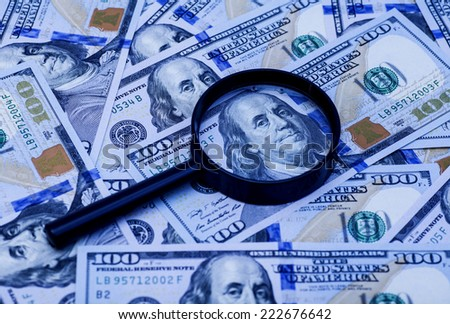 Hundred dollar banknote under magnifying glass, cool tone  - stock photo