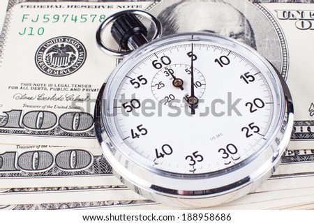 Hundred dollar banknotes with analog silver stopwatch close-up - stock photo