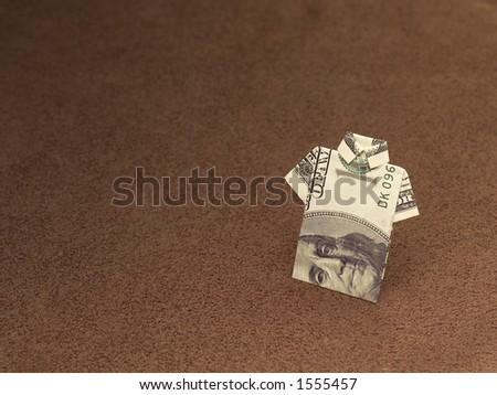 Hundred dollar bill folded into a shirt - stock photo