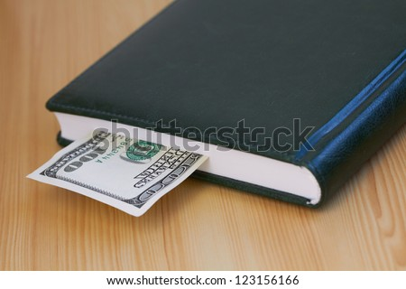 Hundred dollar bill lying in the notebook - stock photo