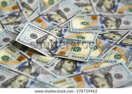 hundred dollar bill on a pile of money - stock photo