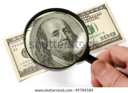 Hundred dollar bill under a magnifying glass is being inspected Conceptual photo isolated on white background - stock photo