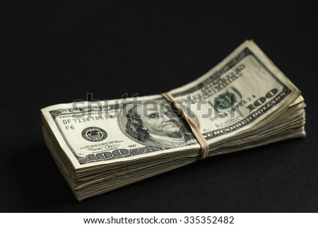 Hundred dollar bills held together with a rubber band. Shallow depth of field with the focus on the near corner 100.  - stock photo