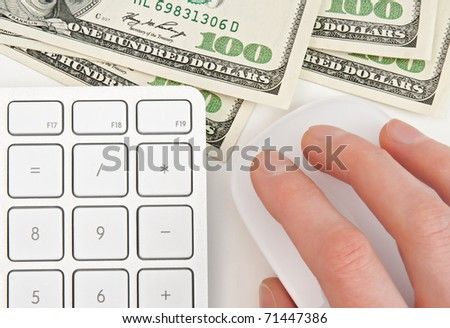 Hundred dollar bills, keyboard calculator and female hand on computer mouse. - stock photo