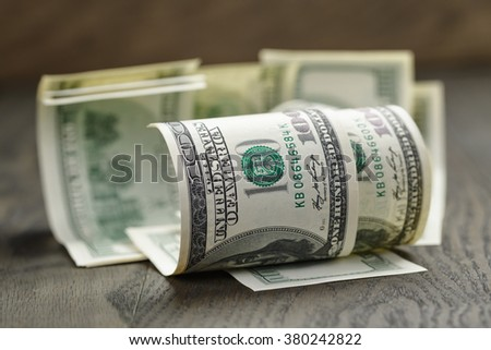 hundred dollar bills on wood table, shallow focus