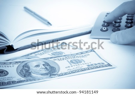 Hundred-Dollars bills, hand pressing keys on the calculator and open notebook - stock photo