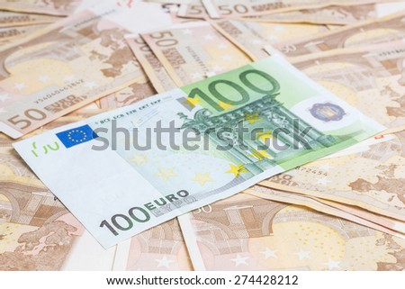 Hundred euro banknote on a group of fifty euros background - stock photo