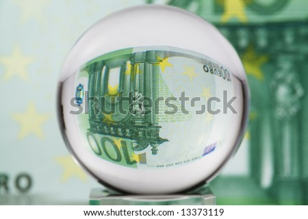 Hundred euro banknote through glass sphere. Blur background. - stock photo