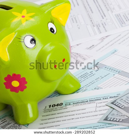 Hundred USA dollars banknote and piggy bank over US tax form - close up shot - stock photo