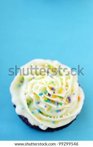 Hundreds and thousands sprinkled on buttercream frosting on a blue background with lots of copyspace - stock photo