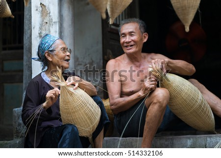 Hung Yen, Vietnam - July 9, 2016: Couple craftsmen making traditional bamboo fish trap at her old house in Thu Sy trade village