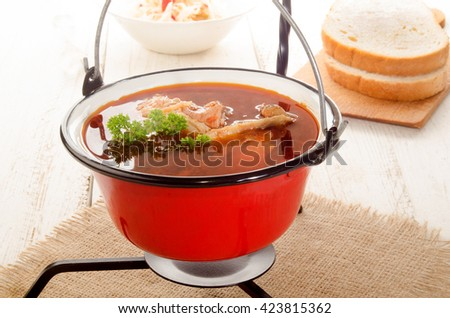 hungarian carp soup in a small red kettle and sour salad - stock photo