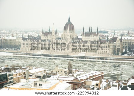 Hungarian parliament building at winter, ice drift on Danube river (Budapest) - stock photo