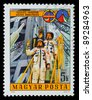 HUNGARY - CIRCA 1986: A stamp printed in Hungary commemorating Soviet-Hungarian cooperation on space exploration. Two cosmonauts/astronauts waving from the launch platform, circa 1986 - stock photo