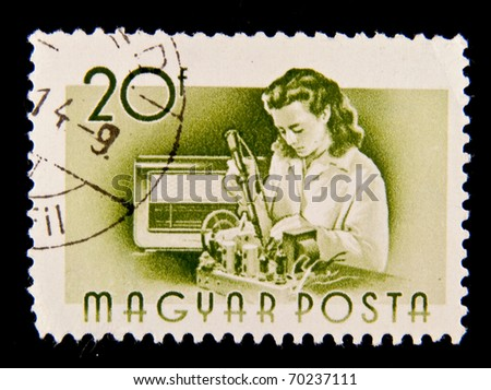 HUNGARY - CIRCA 1955: A stamp printed in Hungary showing woman repairing a device, circa 1955 - stock photo