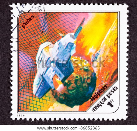 HUNGARY - CIRCA 1978:  An airmail stamp printed in Hungary shows a futuristic space ship around Phobos, the Martian moon, circa 1978. - stock photo
