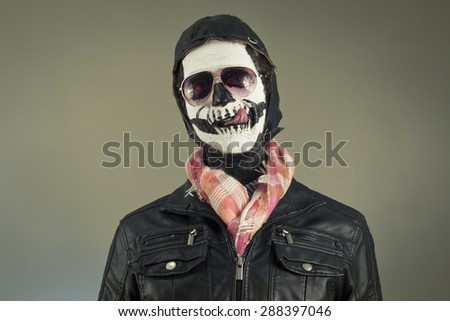 Hungry aviator with face painted as human skull - stock photo