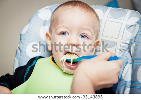 Hungry baby boy eating soup - stock photo