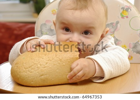 hungry baby eating the fresh bread - stock photo
