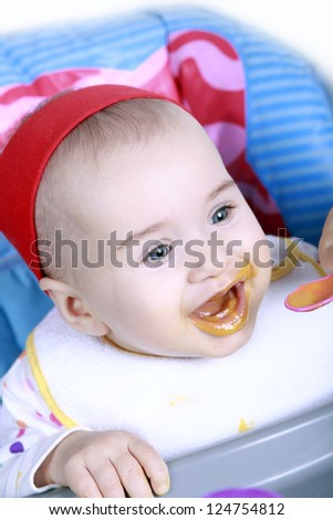 Hungry baby girl enjoy her lunch - stock photo