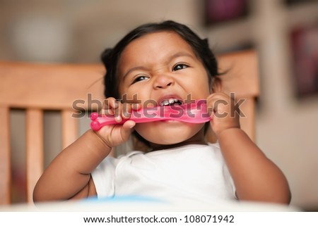 hungry baby putting a spoon to her mouth and biting it - stock photo
