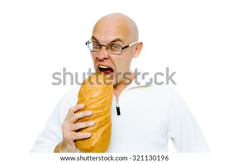 Hungry bald man with glasses bites a a large loaf. Studio. isolated - stock photo