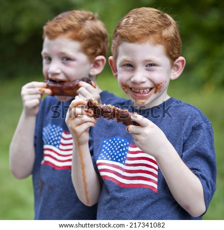 Hungry boys eating BBQ rib outside - stock photo