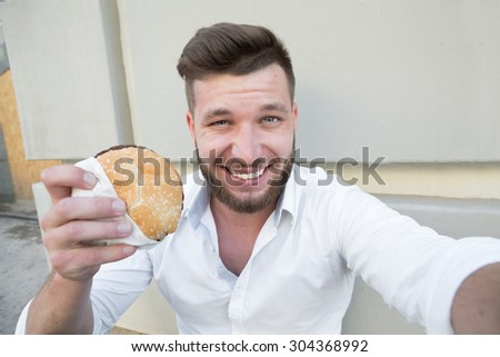 Hungry businessman making selfies with hamburger during his lunch time. Smiling short-haired man resting outdoors. - stock photo