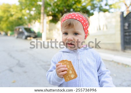 hungry child eating biscuit in street - stock photo