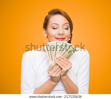 Hungry for money. Portrait, greedy executive, CEO, boss, corporate employee, holding, smelling dollar banknotes tightly, isolated orange background. Human emotion facial expression life perception - stock photo