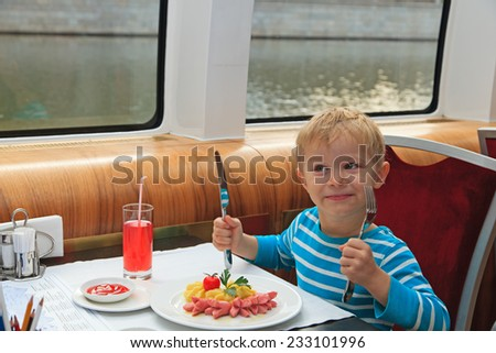 hungry little boy eating in restaurant - stock photo
