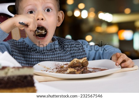 Hungry little boy gobbling down a slice of tasty chocolate cake with his mouth open wide for a mouthful as he sits at a table in a restaurant - stock photo