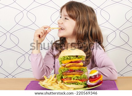 hungry little girl eat french fries and big hamburger - stock photo