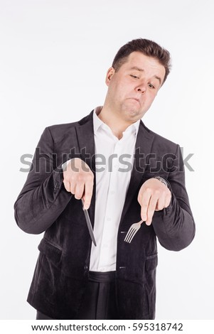 hungry man holding cutlery fork and knife on hand. diet, food, healthy, style concept. isolated on a gray studio background.