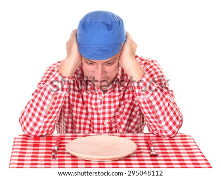 Hungry man is looking in his empty plate - stock photo