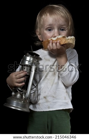 hungry poor child with bread and oil lamp - stock photo