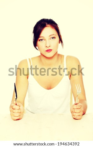 Hungry pretty caucasian teenage girl sitting behind the table with fork and knife. - stock photo