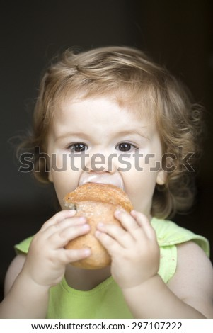 Hungry small beautiful baby boy with blonde curly hair holding and eating fresh tasty bread roll on black backdroung, vertical picture - stock photo