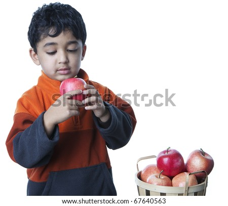 Hungry Toddler Eating Apple From Among a Basket of Fruit, Isolated, White - stock photo