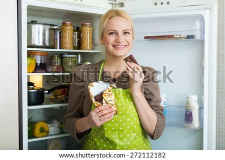 Hungry woman near opening fridge eating a chocolate  - stock photo