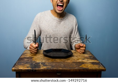 Hungry young man is screaming for his dinner - stock photo
