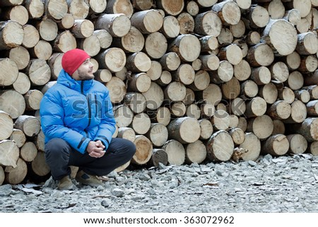 Hunkering worker having a rest at pile of logged firewood background outdoors in winter mountain forest - stock photo