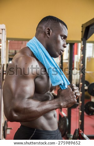 Hunky muscular black bodybuilder working out in gym, resting after exercise - stock photo