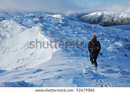 hunter hiking through snow - stock photo