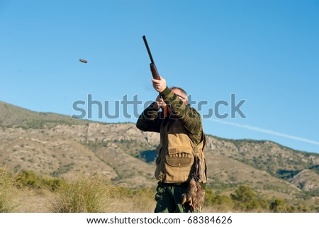 Hunter in action aiming and shooting his rifle - stock photo