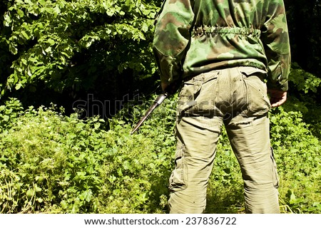 Hunter is holding a knife in his hand at forest from the back - stock photo