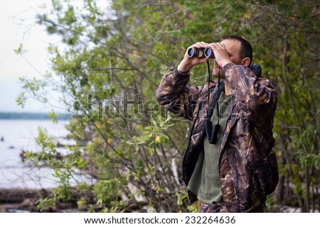 hunter looking through binoculars  - stock photo